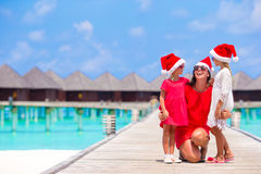 Young mother and little girls in Santa hat on Christmas holidays. At Maldives Royalty Free Stock Photography