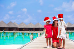 Young mother and little girls in Santa hat on Christmas holidays. Young mother and little girls in Santa hat at tropical beach Royalty Free Stock Image