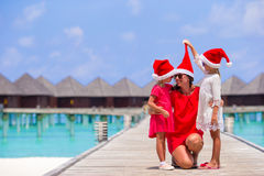 Young mother and little girls in Santa hat Royalty Free Stock Photography