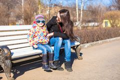 Young mother and little happy girl relax in spring park at sunny day Royalty Free Stock Images