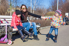 Young mother and little happy girls relax in spring park at sunny day Royalty Free Stock Photo