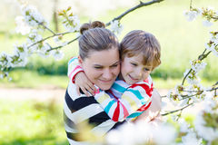 Young mother and little kid boy having fun in blooming garden stock photos