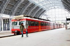 Young mother and little kid walk through the Bergen train station platforms with typical red Voss train on background, Bergen. stock photography
