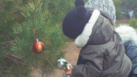 A young mother and little son decorate the Christmas tree outdoors. Portrait loving family close up. Concept Merry. Christmas and Happy Holidays stock video footage