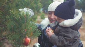 A young mother and little son decorate the Christmas tree outdoors. Portrait loving family close up. Concept Merry. Christmas and Happy Holidays stock video