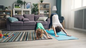 Mother and little son doing yoga together at home relaxing enjoying activity. Young mother and little son are doing yoga together at home relaxing enjoying stock video footage
