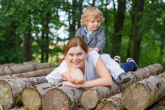 Young mother and little son having fun in summer forest. Royalty Free Stock Image