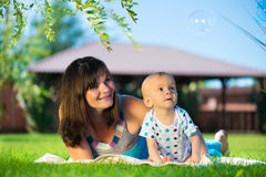 Young mother and little son looking at soap bubbles Stock Photo