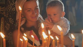 Young mother with little son observes a burning candles in church stock video