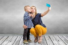 Young mother and little son are photographed on a mobile phone making selfie.Family leisure,entertainment and fun. royalty free stock images