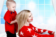 Young mother and little son playing.Child combs mom`s hair.The concept of a family holiday. Mom and small son play,spend time together royalty free stock photo