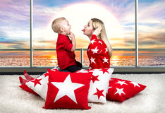 Young mother and little son playing . The concept of a family holiday. Beautiful pillows to decorate the interior of the house. The concept of a family holiday royalty free stock images