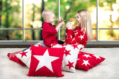Young mother and little son playing . The concept of a family holiday. Beautiful pillows to decorate the interior of the house. The concept of a family holiday stock photos