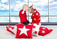 Young mother and little son playing . The concept of a family holiday. Beautiful pillows to decorate the interior of the house. Mom and son playing,having fun royalty free stock image