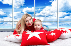 Young mother and little son playing lying on the pillow. The concept of a family holiday. Beautiful cushions for home interior dec. The concept of a family stock images