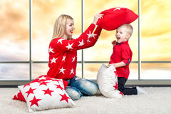 Young mother and little son playing with pillows,pillow fight. The concept of a family holiday.Beautiful pillows to decorate the i. The concept of a family stock image