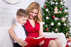 Young mother and little son reading book in front of Christmas t Stock Images