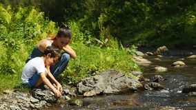 Young Mother And Little Son Sitting At The Mountain Stream Playing With Stones stock video