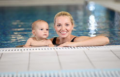 Young mother and little son in a swimming pool. Young cheerful mother and little son in a swimming pool Stock Images