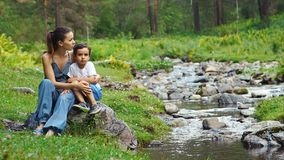 Young Mother And Little Son Talking And Sitting At The Mountain Stream stock video