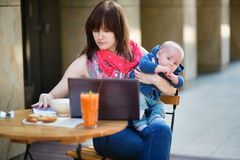 Young mother with little son working on her laptop. In a cafe Stock Images