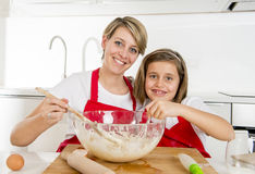 Young mother and little sweet daughter in cook apron cooking together baking at modern home kitchen Royalty Free Stock Images