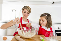 Young mother and little sweet daughter in cook apron cooking together baking at modern home kitchen Royalty Free Stock Photos