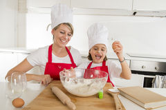 Young mother and little sweet daughter in cook hat and apron cooking together baking at home kitchen Royalty Free Stock Photo