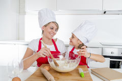 Young mother and little sweet daughter in cook hat and apron cooking together baking at home kitchen Stock Image
