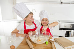 Young mother and little sweet daughter in cook hat and apron cooking together baking at home kitchen Stock Photos