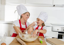 Young mother and little sweet daughter in cook hat and apron cooking together baking at home kitchen Royalty Free Stock Photography