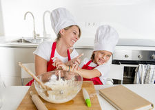 Young mother and little sweet daughter in cook hat and apron cooking together baking at home kitchen Royalty Free Stock Images