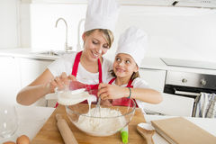 Young mother and little sweet daughter in cook hat and apron cooking together baking at home kitchen Royalty Free Stock Image