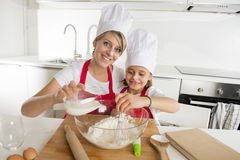 Young mother and little sweet daughter in cook hat and apron cooking together baking at home kitchen Royalty Free Stock Photos