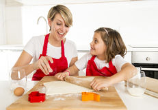 Young mother and little sweet daughter cooking in kitchen preparing desert with rolling pin rod stock image