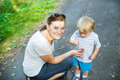 Young mother and little toddler boy eating wild berries in fores Royalty Free Stock Photos