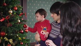 Young mother with long black hair, in a smart dress makes your little son to decorate a gorgeous Christmas tree. Dad stock video
