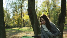 Young mother with long hair with green baby carriage in the park in autumn. The girl in an autumn coat and warm mittens cold. Bright sun penetrates through the stock footage