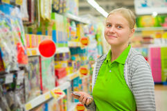 Young mother look at shopping list in phone in supermarket Royalty Free Stock Photos