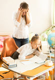 Young mother looking daughter sleeping while doing homework Royalty Free Stock Photos