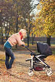 A young mother looking at her baby in a stroller Stock Photos