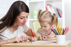 Young mother looking how her kid daughter drawing a picture Royalty Free Stock Image