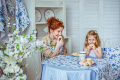 Young mother is looking to her little daughter. A young mother is looking to her little daughter on a kitchen Royalty Free Stock Images