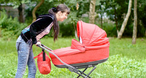 Young mother looks in a baby carriage Stock Image