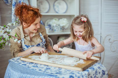Young mother looks at her little daughter how she works. A young mother looks at her little daughter how she is rolling a dough Stock Image