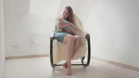 Young mother is lulling her son to sleepin a rocking chair. stock video footage