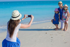 Young mother making photo on phone of her family at the beach Royalty Free Stock Image