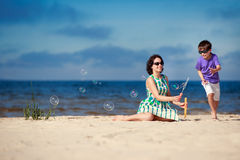 Young mother making soap bubbles with his child Royalty Free Stock Image