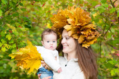 Young mother in maple leaf wreath with baby. Attractive young mother holding a baby girl in a forest with a maple leaves wreath Stock Image