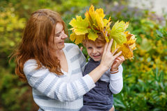 Young  mother in a maple leaf wreath holding little toddler boy. In autumn park Stock Photography